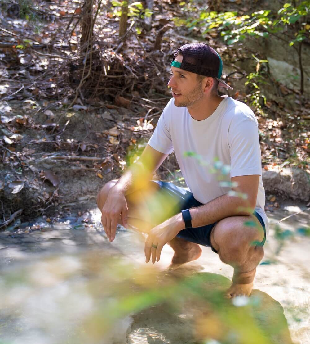 Shawn Tolleson sitting on a rock in a river